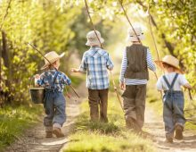 Four boys with fishing rods go on a fishing trip on the narrow rural road in sunny summer day